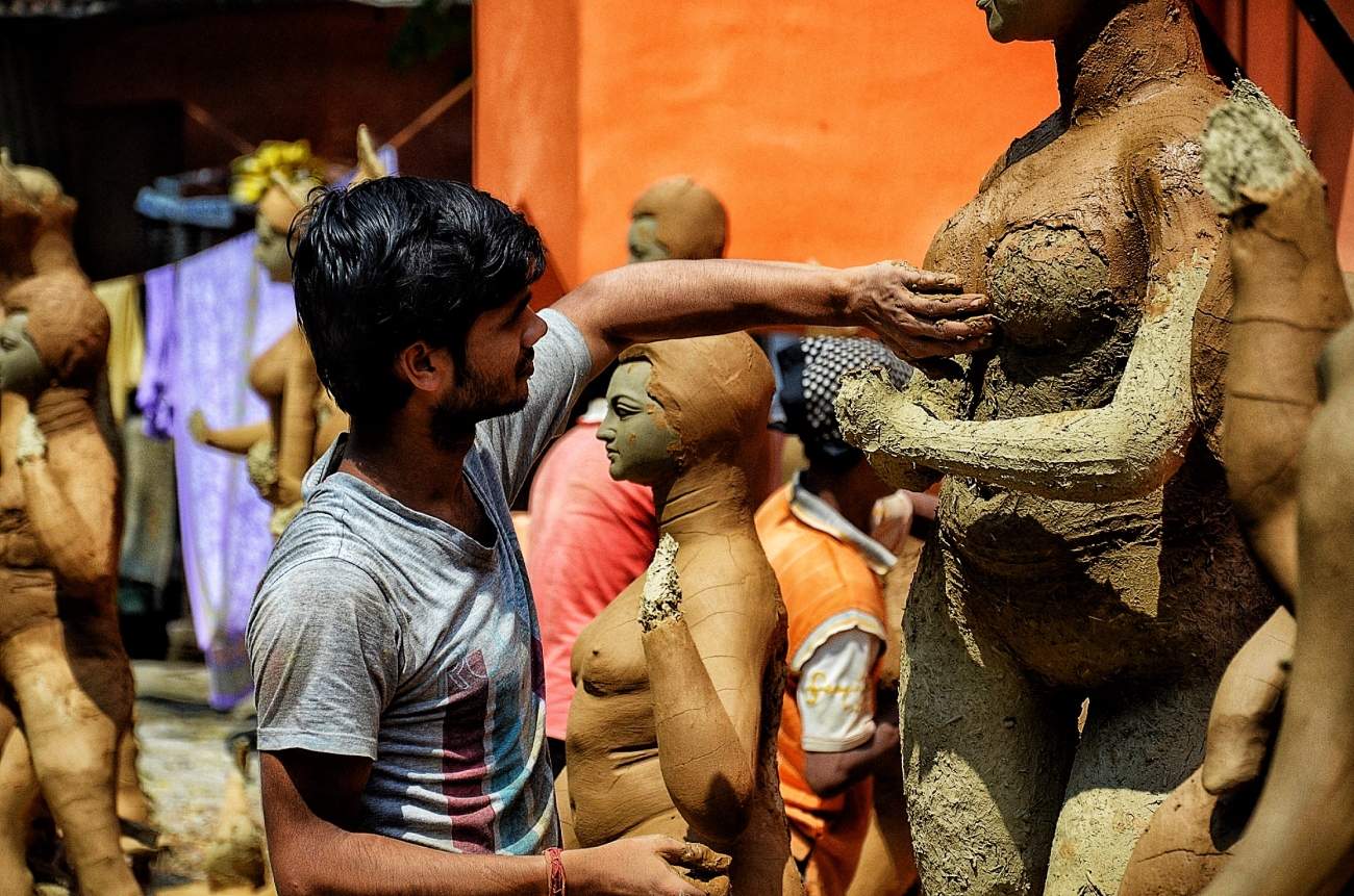 An idol maker from Bengal working on an idol for Durga Puja