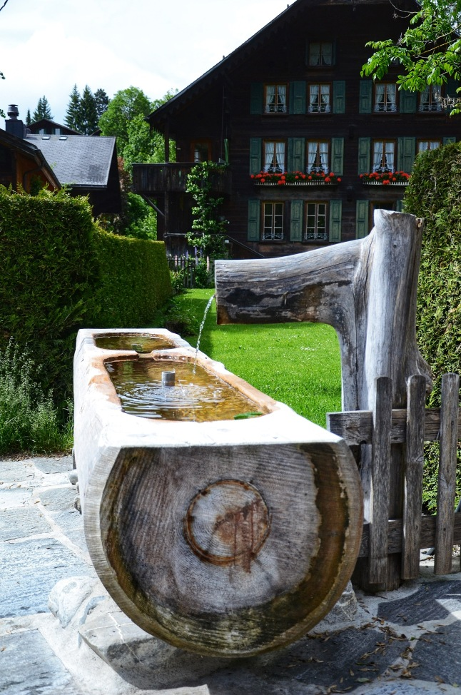 A wooden water fountain in Gstaad