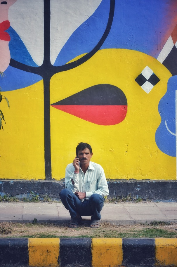 Going Mobile - A man takes a call in front of a bright mural at Lodi Art District